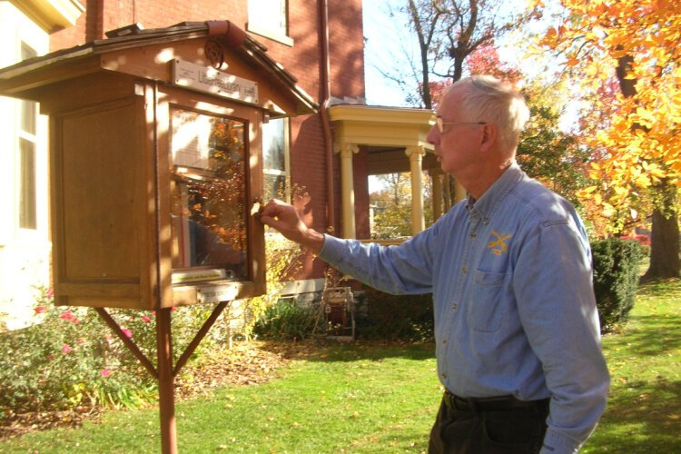 Bill Dean tends to his Westwood Little Free Library, charter #19336.