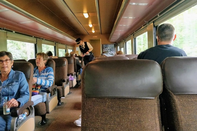 Riders sit in a coach car originally built for the Delaware, Lackawanna, and Western Railroad in 1930 by the famed Pullman Company.